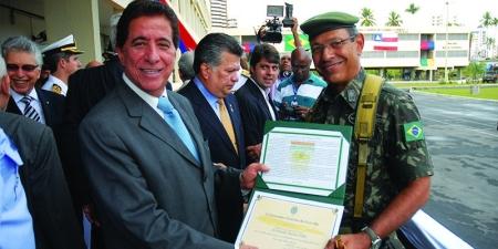 ... há que, goste. Na foto, o secretário recebe um diploma de reconhecimento das mãos de um militar.